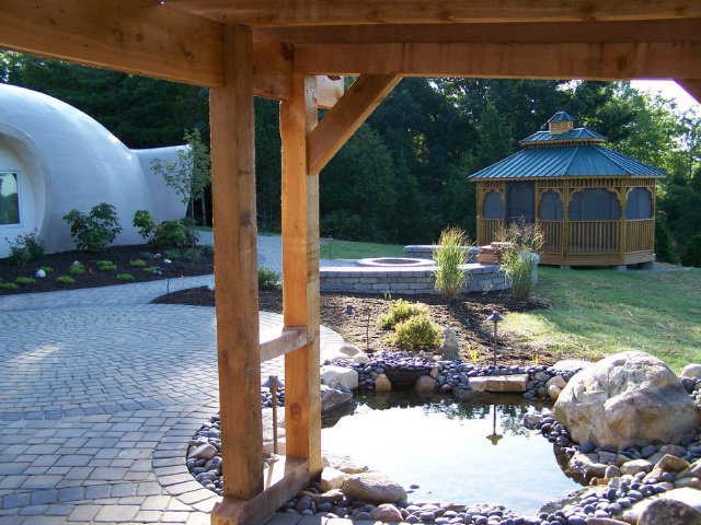Natural balance — Water, plants, and wood structures balance the hard dome