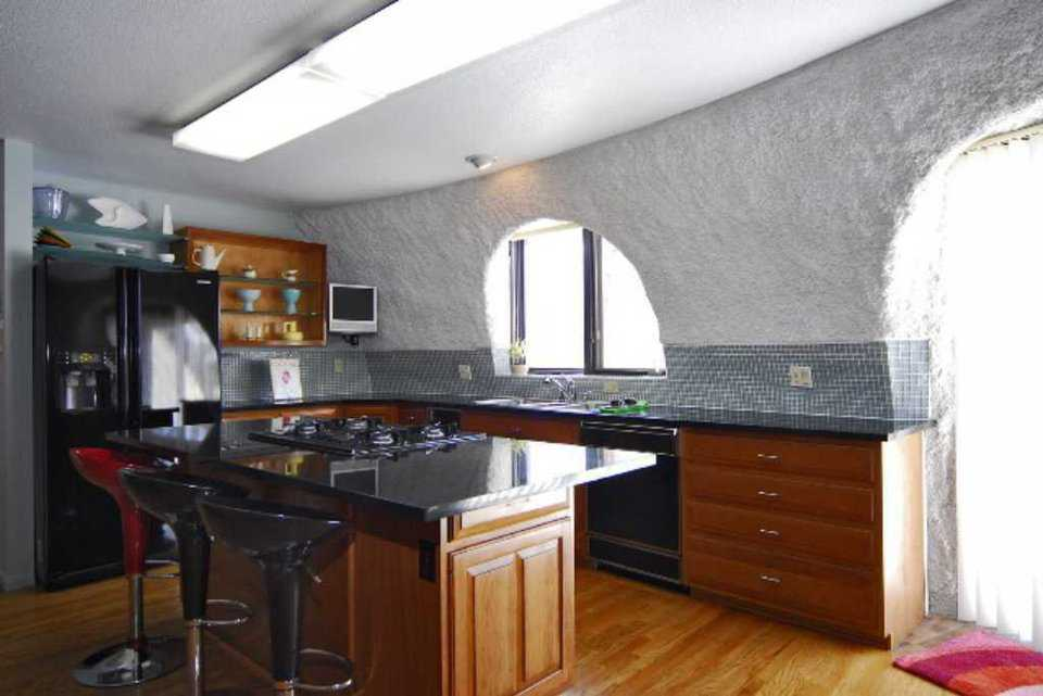 Kitchen — The gourmet kitchen has black slab, granite countertops, custom cabinets, a center island and a planning desk.