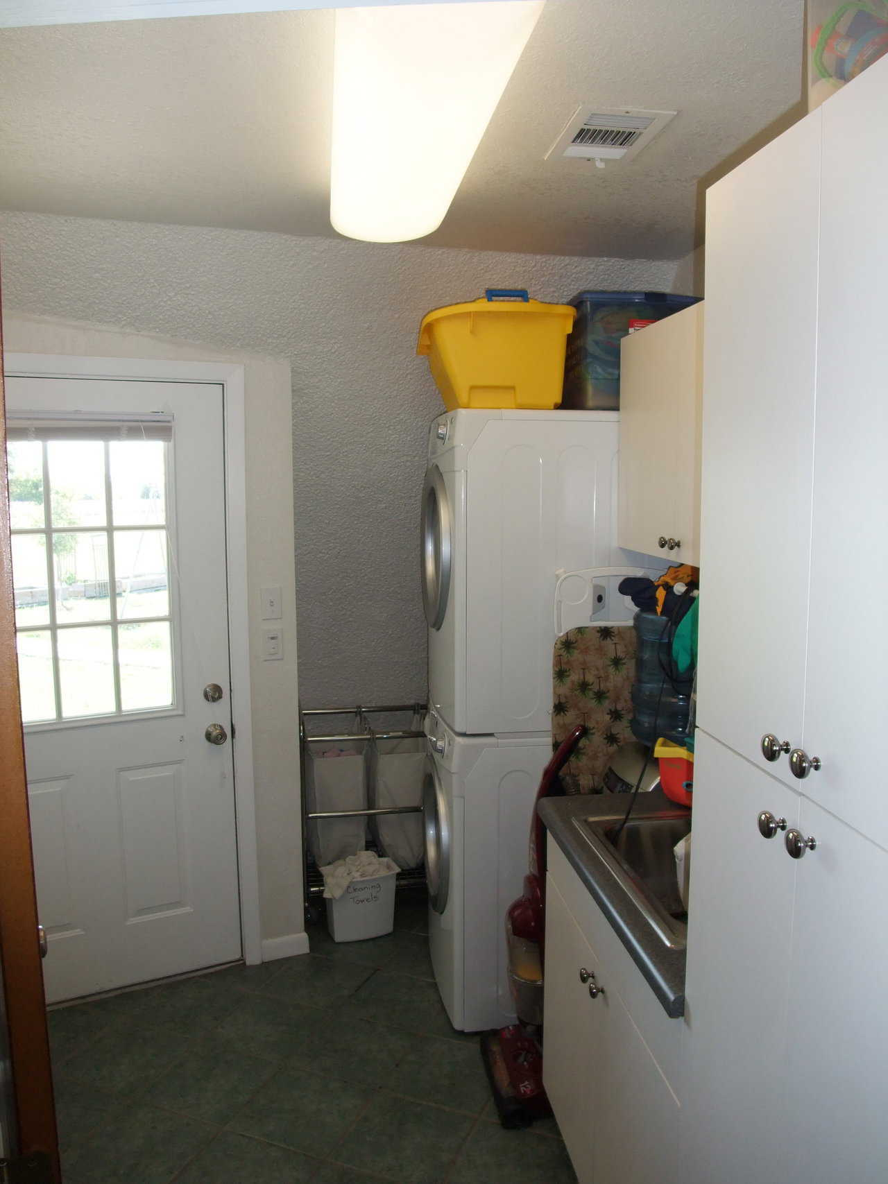 Laundry area — in addition to the washer and dryer, it includes a sink and storage cabinets.