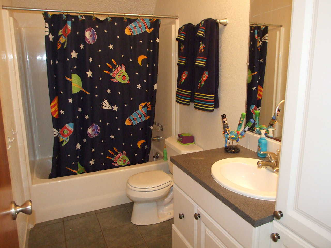 Bathroom — It includes a shower curtain and towels with an outer space design.