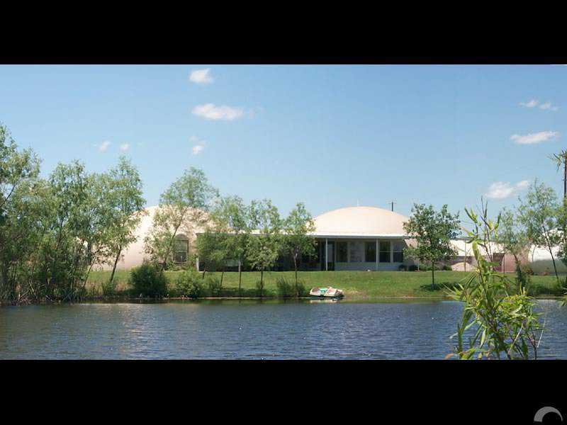 House by the pond — Charca is the Spanish word for pond and Casa means house. This acre pond provides  a spectacular backdrop for its dome-home.