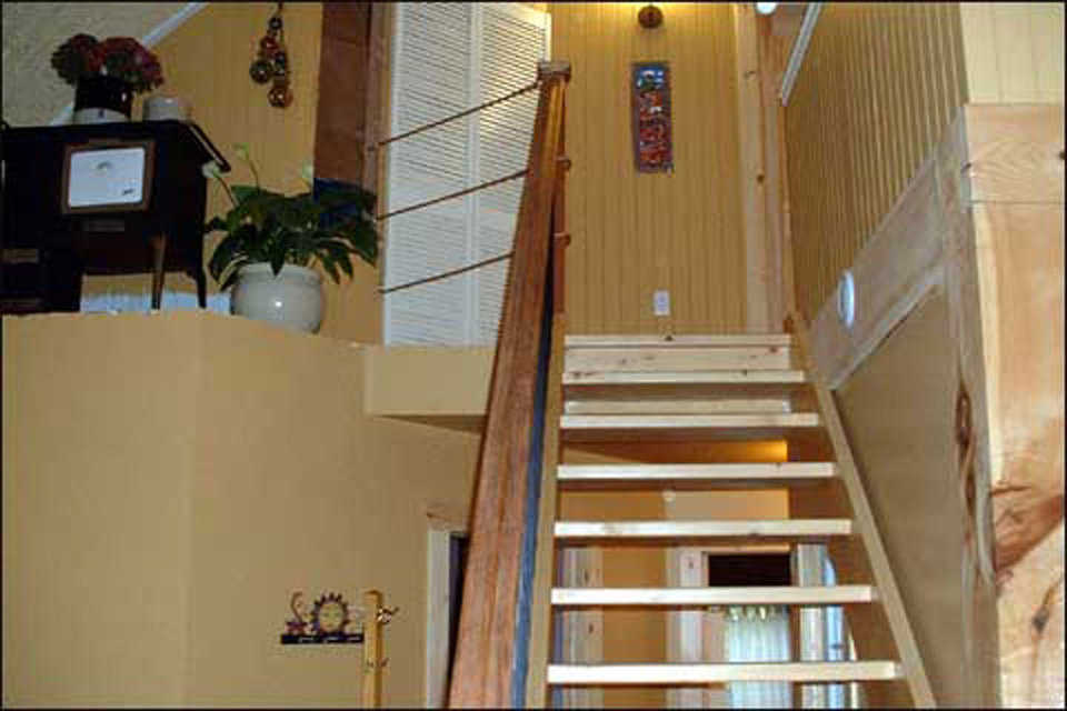 Going Up — A staircase leads to the upper bedrooms and loft.