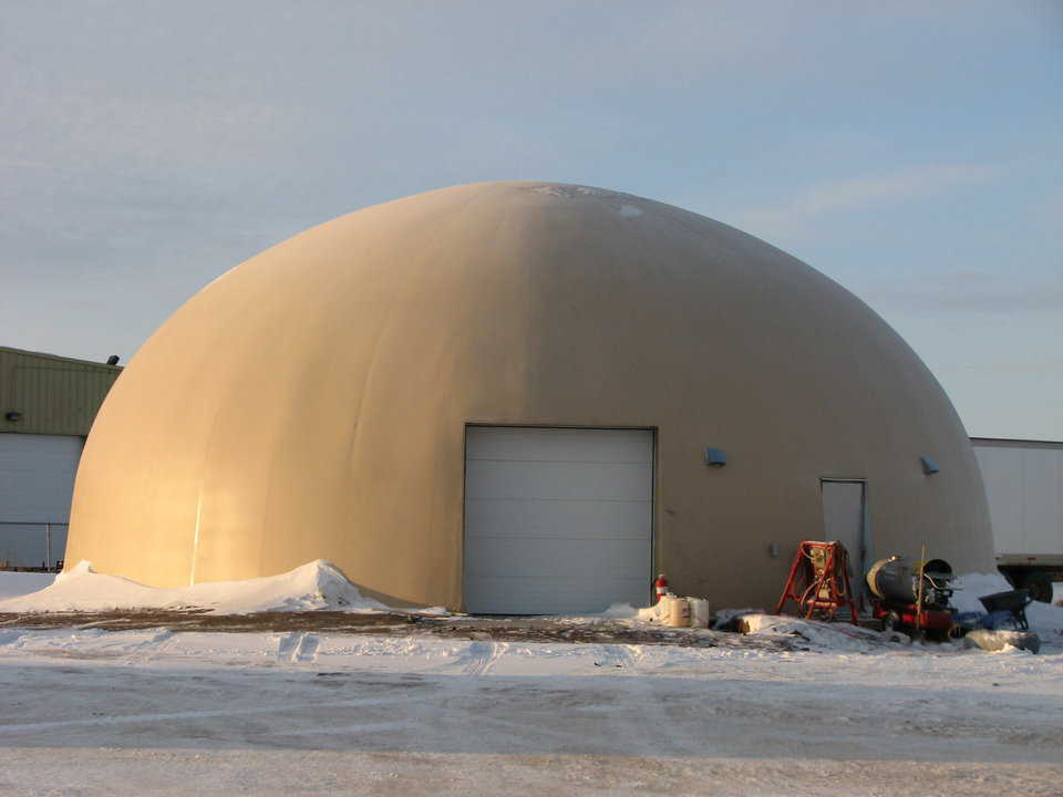 Figure 2.9 — Heated Monolithic Dome shop in Sasketoon, Saskatchewan, Canada.  The outside temperature at this time was 13 degrees Fahrenheit below zero (-25C). This is a standard color photograph taken by a standard camera.  Note the metal buildings in the background.