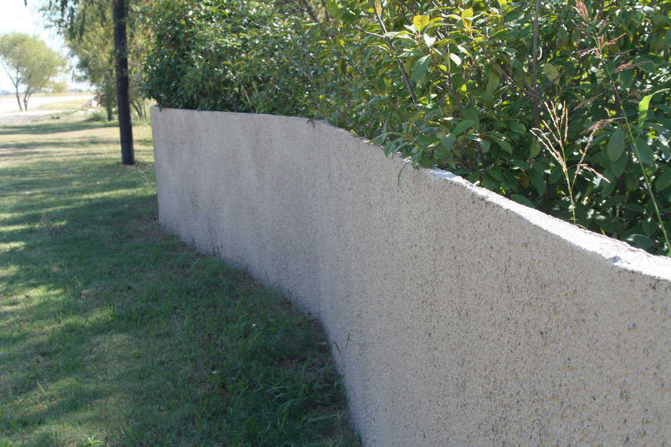 "Monolithic Fences — Monolithic uses single side forms and our shotcrete equipment to make great fences.  This concrete fence is only 2"" thick."