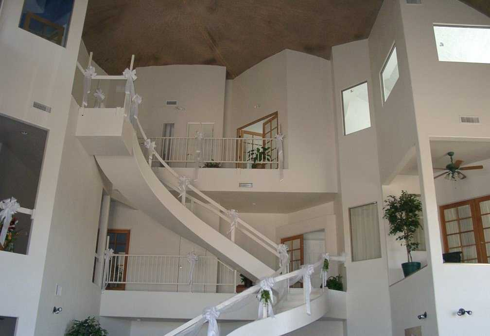 Yuma Dome in Yuma, Arizona  — This staircase leads to the second and third levels in this multigenerational dome that encompasses eight suites, each with at least one bedroom, bathroom, sitting room, laundry area and closets. Dome has 3 stories, 84' diameter, 40' inside height, 11,000 square feet of living space.