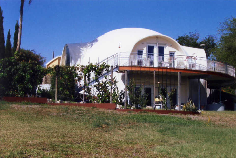 Graceful Curves — This beautiful Monolithic Dome home was also designed and constructed with an integrated stemwall