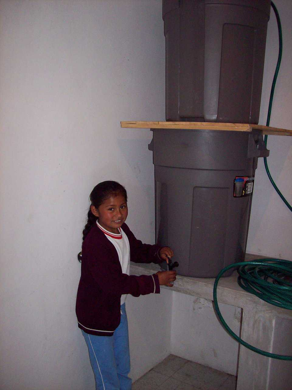 Easy to use! — A girl in Paraquay gets water filtered through a Just Water Ceramic Drip Filter system made with plastic trash cans.