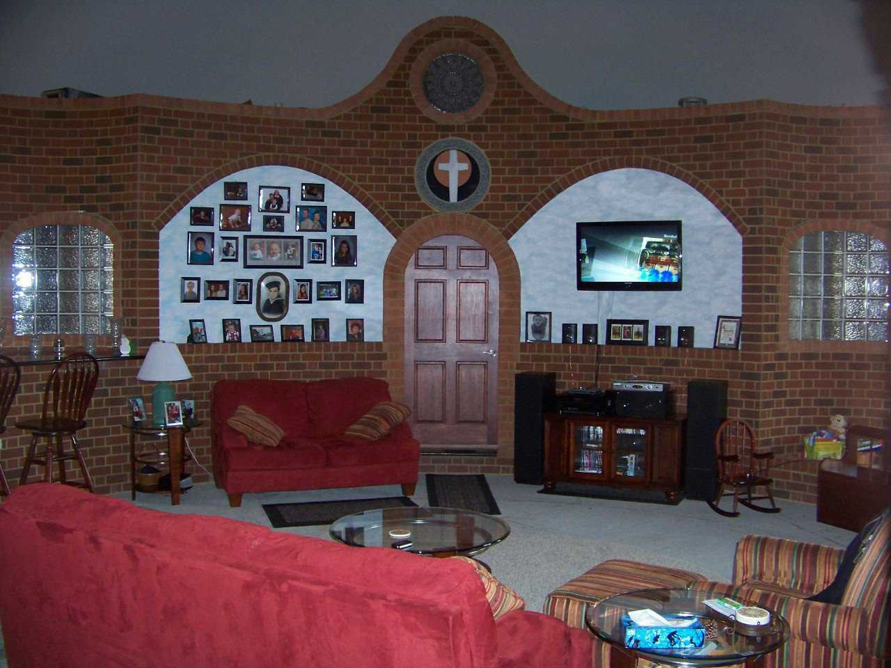 A den of fond memories — Accented by their curved brick arches, the den walls display a collection of family photos.