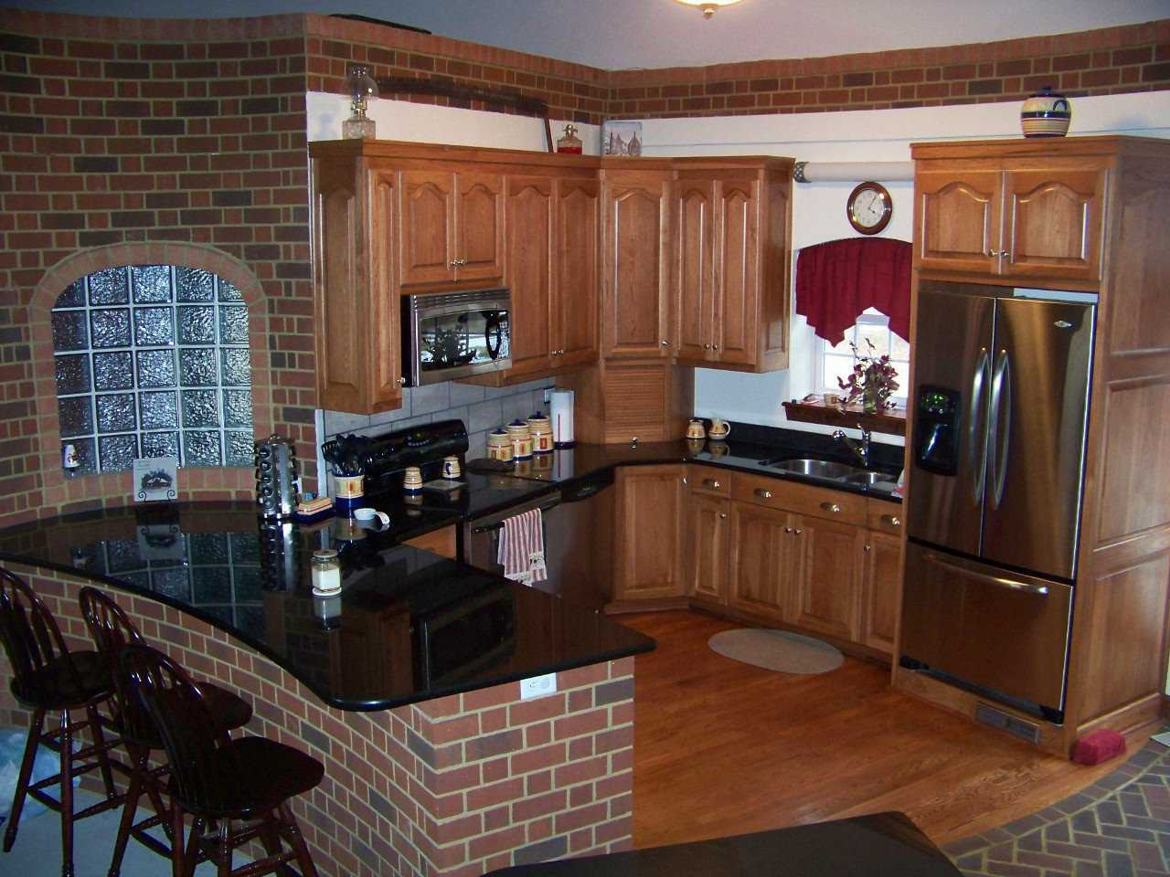 Homey, efficient kitchen — The warm reds and browns in the wood and brick make this an inviting cooking area.