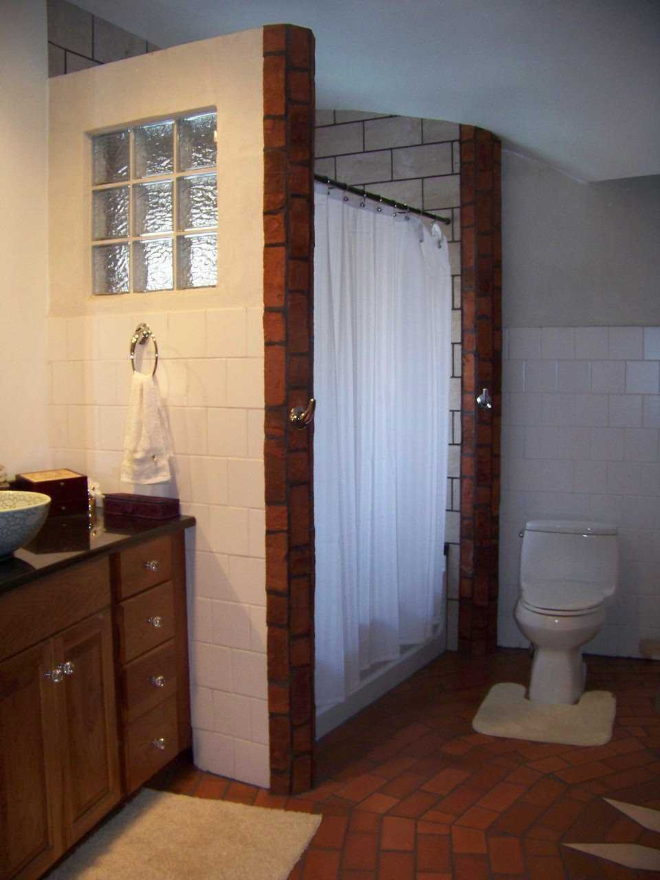 Tile shower — This bathroom sports tile walls and a brick floor with an eye-catching design.