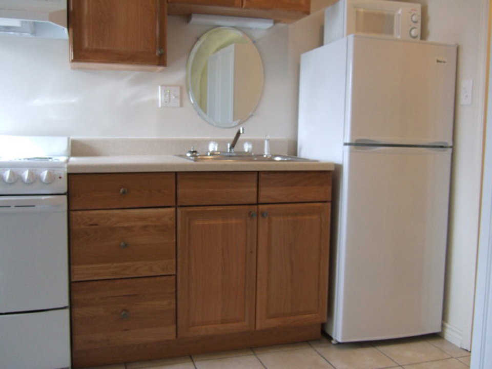 Kitchen — It includes a refrigerator, stove, microwave and cabinets.