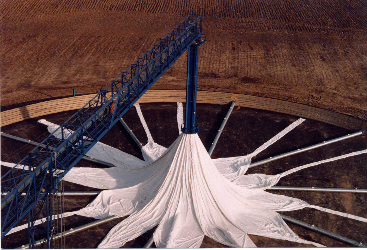 Partially assembled grain cover — Each of the gores (sections) is fastened to a lifting ring around the center tower. As the lifting ring rises, the gores attach to each other.