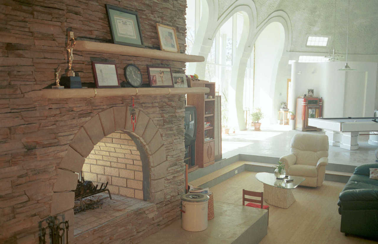 Window wall — Large, store-front windows open onto a gorgeous view. Window wall is 30' wide and 16' high. Arches are 8' wide and 15' high. Glass panels measure 5′ × 8′. Jim hand-formed the fireplace mantel using a stuccolike material.