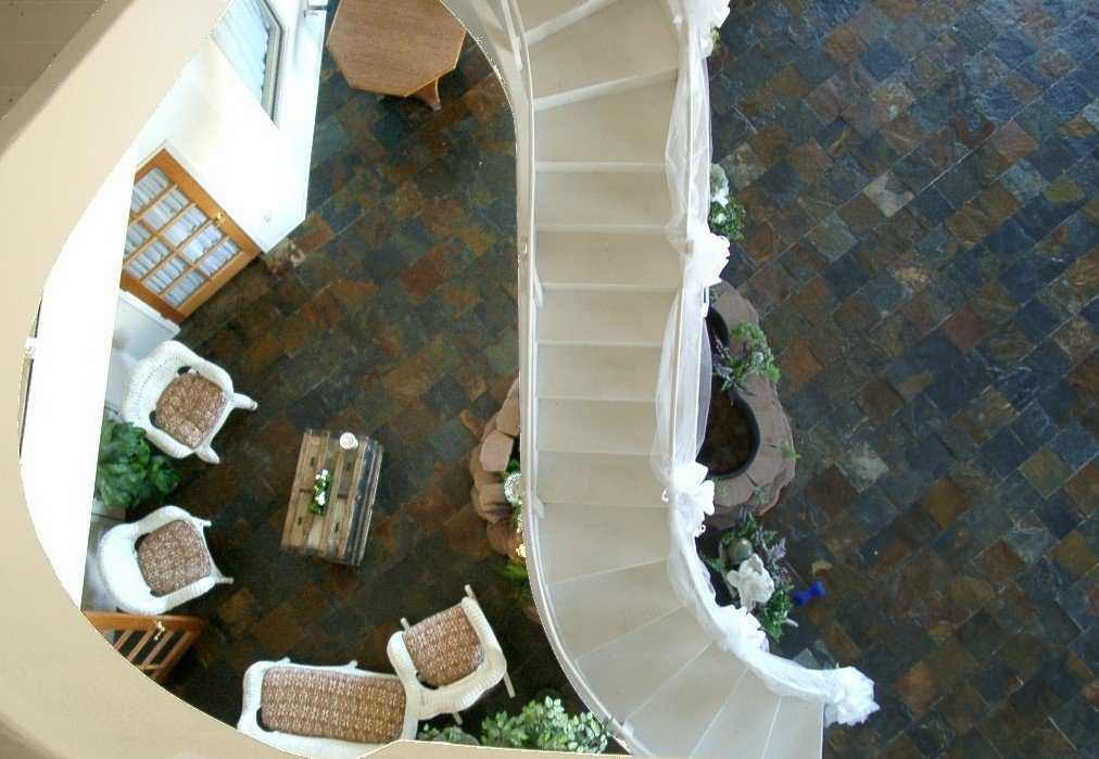View from the third floor — Stone tile flooring provides an earthy-feel and generates a striking contrast to the white staircase and wicker furniture.