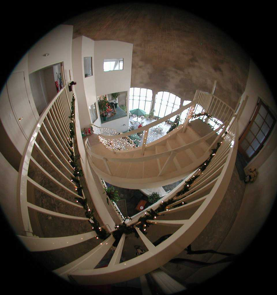 "Deck the halls — View from the top using another ""fish-eye"" lens. Christmas lights and decorations adorn the staircase."