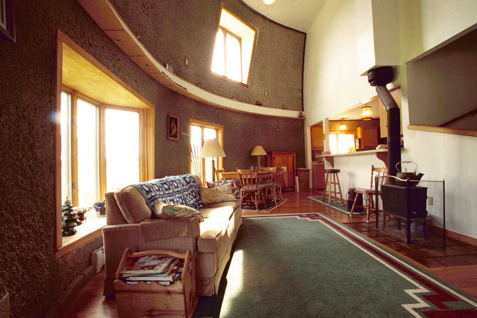 Living room — It's on the main floor and includes a small, wood-burning stove. The owners are not expecting to use the stove. Instead, they rely on a hot water system running along the floor of each level.
