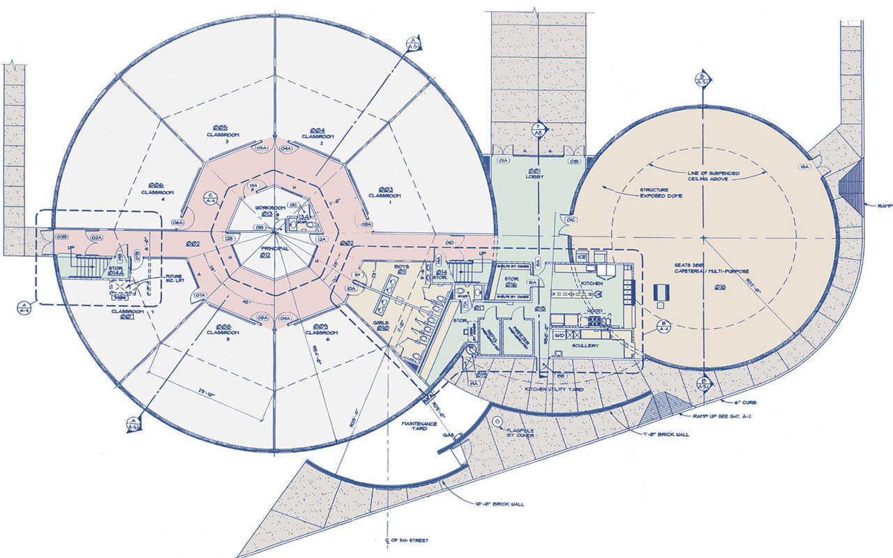 Floor plan — Larger dome encompasses 7 classrooms arranged around a central office area and a large upstairs library. Smaller dome houses a cafeteria and kitchen.