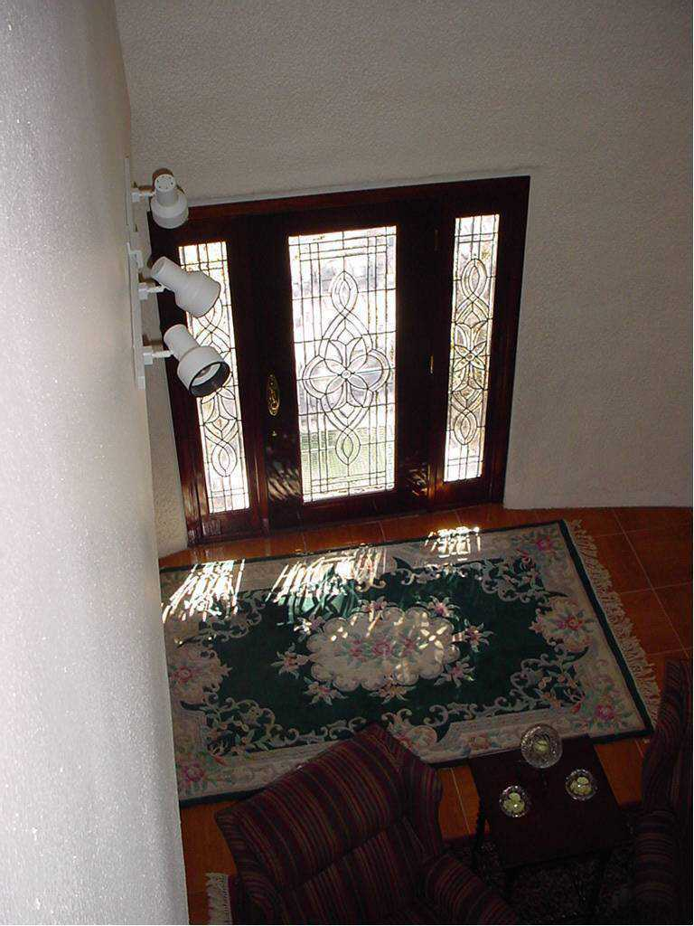 Entryway — A mahogany, leaded glass front door with matching side lights welcomes visitors.