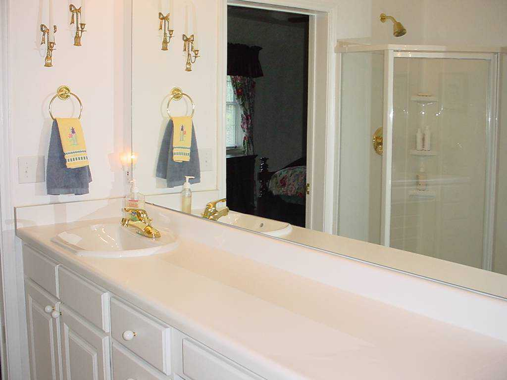 Guest bath — It includes a wall of mirrors and a marble counter top.