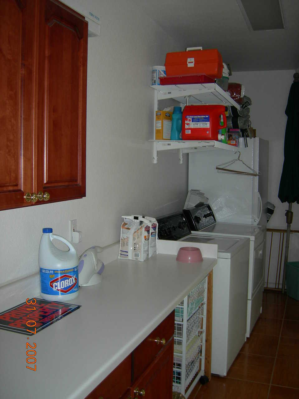 Utility room — Cabinets and hanging shelves provide needed storage.