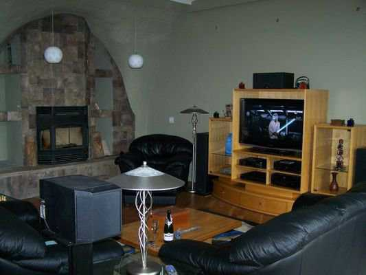 Entertainment area — Besides a wide-screen TV, this entertainment area sports a stone fireplace and soft leather sofas and chairs.