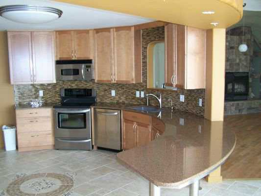 Kitchen — It includes a beautiful tile floor, wood cabinets, stainless steel appliances and a curved, marble-like counter.