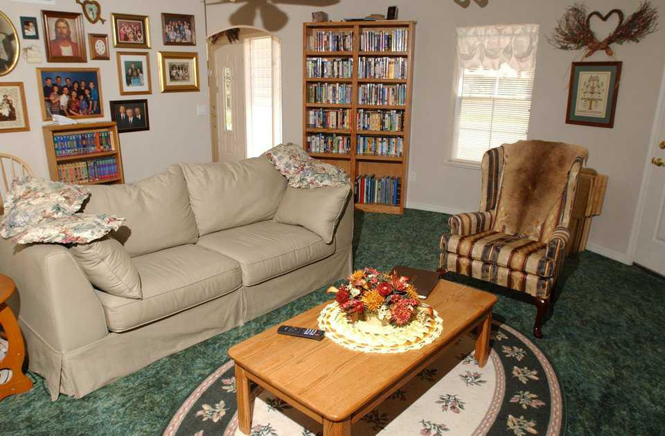 Coziness — Second living area is adjacent to the home's main entryway. Large bookshelves, entertainment center and a deep green carpet add to the room's warmth and comfort.