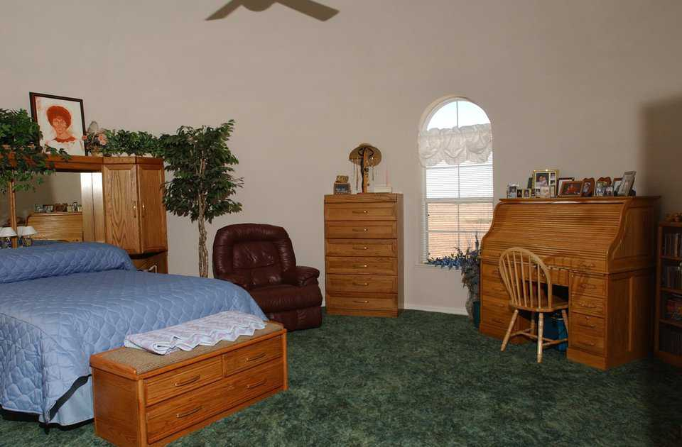 Master bedroom — It has a gracefully arched window and plenty of space for a sitting area and office.