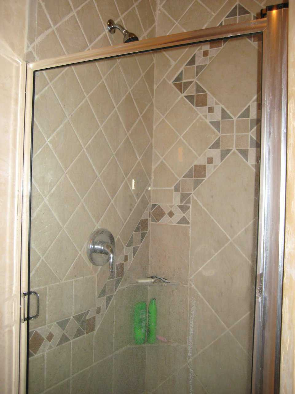 Intricate tile work — Walls with tiles of various colors and sizes form ornate patterns and enclose this shower.