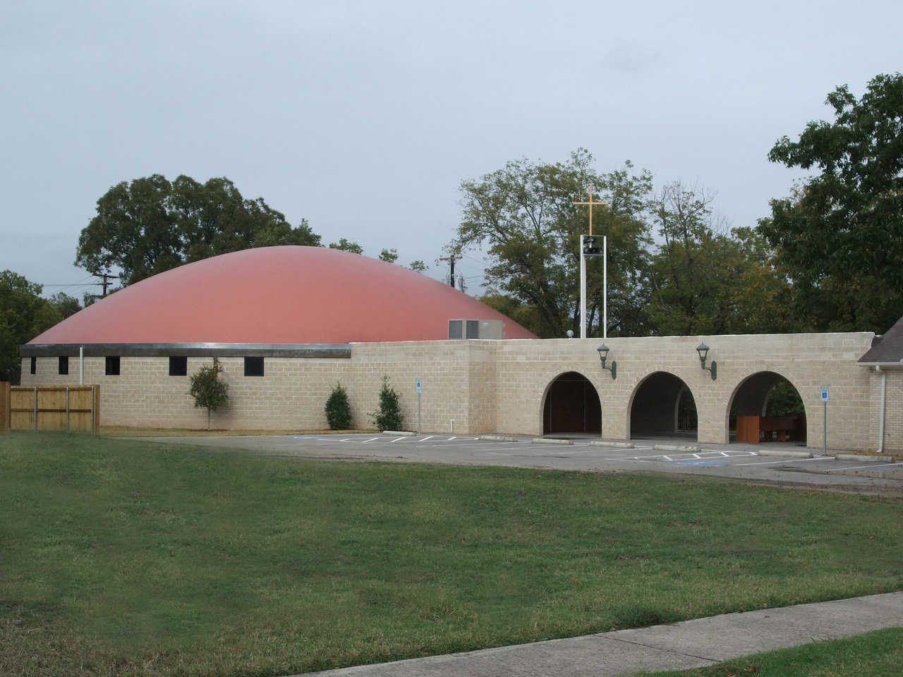 Architectural blending — A long wall connects St. Joseph's new Monolithic Dome church with the original church, a small, traditional structure that now serves as the Parish Hall. Both the connecting wall and the stemwall of the dome are made of cut face block that looks like brick.