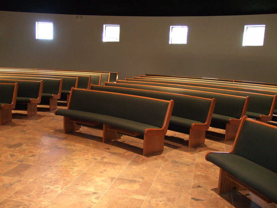Comfortable seating — Curved wooden pews, upholstered with a cushiony soft green fabric, help create an intimate atmosphere while providing ample seating.