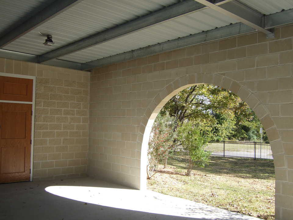 Arched openings — The connecting wall between the new dome-church and the old church has three arched entrances that open onto the covered patio/walkway.