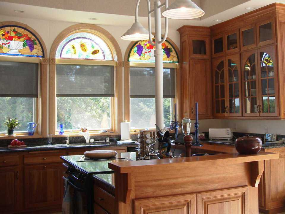 Gourmet Fittings — The kitchen features custom cabinets and stained-glass windows.