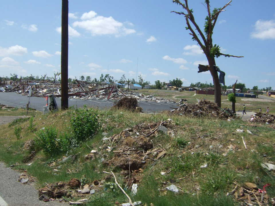 Houses in the background are covered with blue tarps. Although not destroyed, they received severe damage.