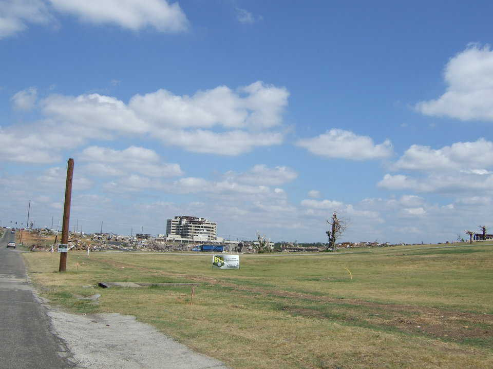 A beyond-salvage hospital is in the background and the area all around it is flattened.