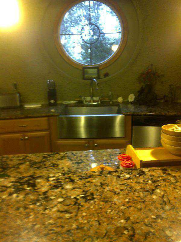 The kitchen has a pretty, round window just above the sink.