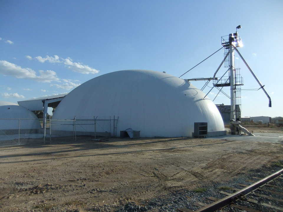 A view of the back — Shown here is the completed facility from the rear. You can see the unloading can be done from the rail or trucks. Product can go back into trucks or into the building. To the left you can see the small dome and the canopy over the mixing facility.