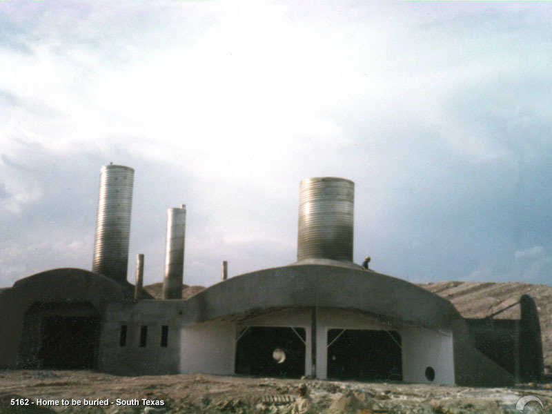 This home under construction. It was built in 1987 and  is truly a nuclear fallout shelter.  The earth cover goes to the top of the pipes.  For more information see the John Ayers article.