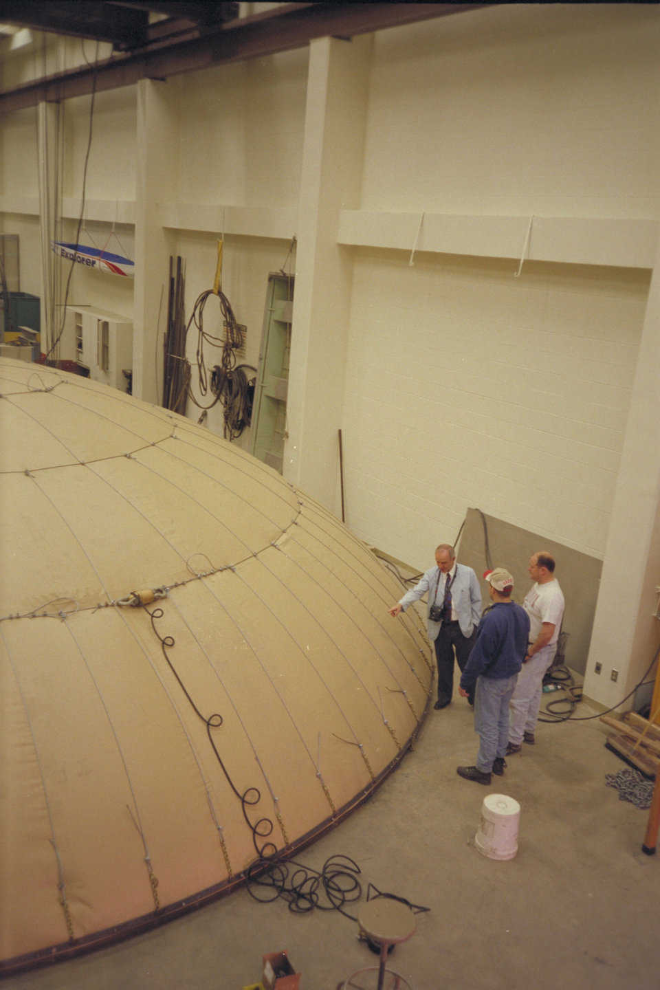 Dr. Wilson and two students examine the Crenosphere test model. A Monolithic Dome built without cables may be built to 296' in diameter. This test showed that a cable restrained dome may achieve domes up to 1000' in diameter.