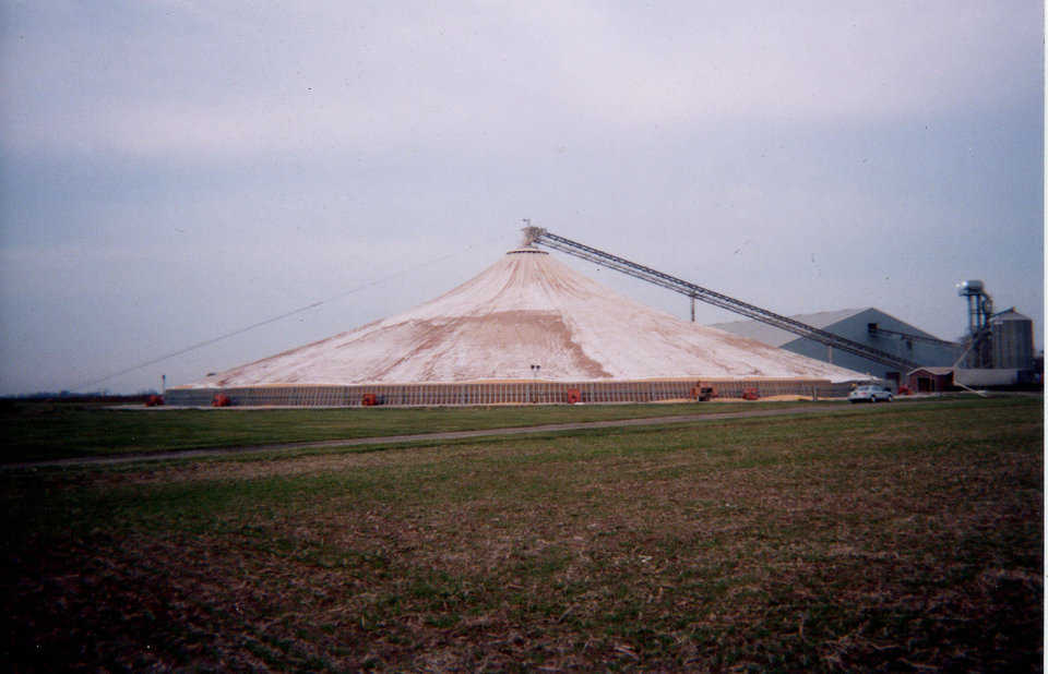 Grain is conveyed to the top of the tower via a conveyor, then dropped down the tower. As grain begins piling under the fabric cover, the lifting ring lifts it. When the fabric reaches its capacity, a cover is fastened over its central opening. Result: A cone-shaped, fabric structure full of protected, stored grain.