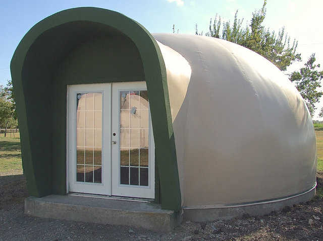 When Mike South built a new, small dome behind his home, he designed and built a tilted-out augment over the front entrance and the windows in back.  The front augment protects the door and provides shelter for folks entering the dome, while the back augment protects the windows.