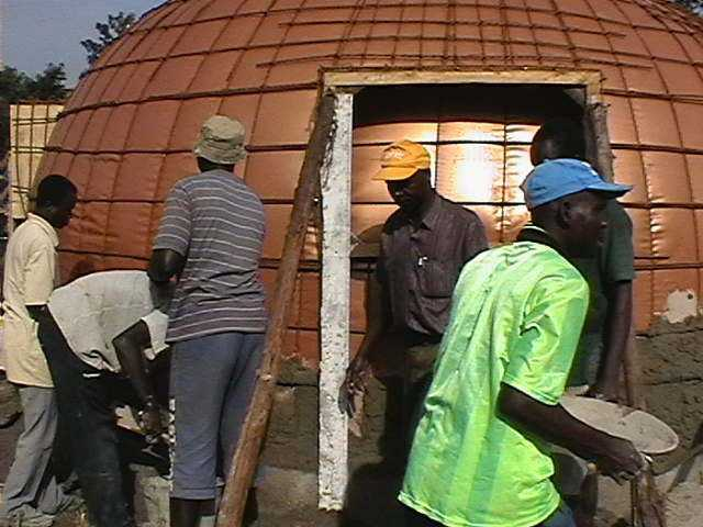 Workers and volunteers apply concrete on an EcoShell.