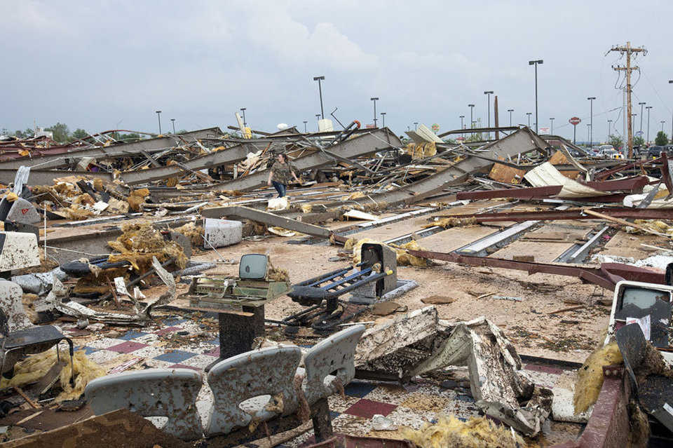 A woman walks through what remains of a bowling alley, and other buildings, after a huge tornado struck Moore, near Oklahoma City, on May 20, 2013.