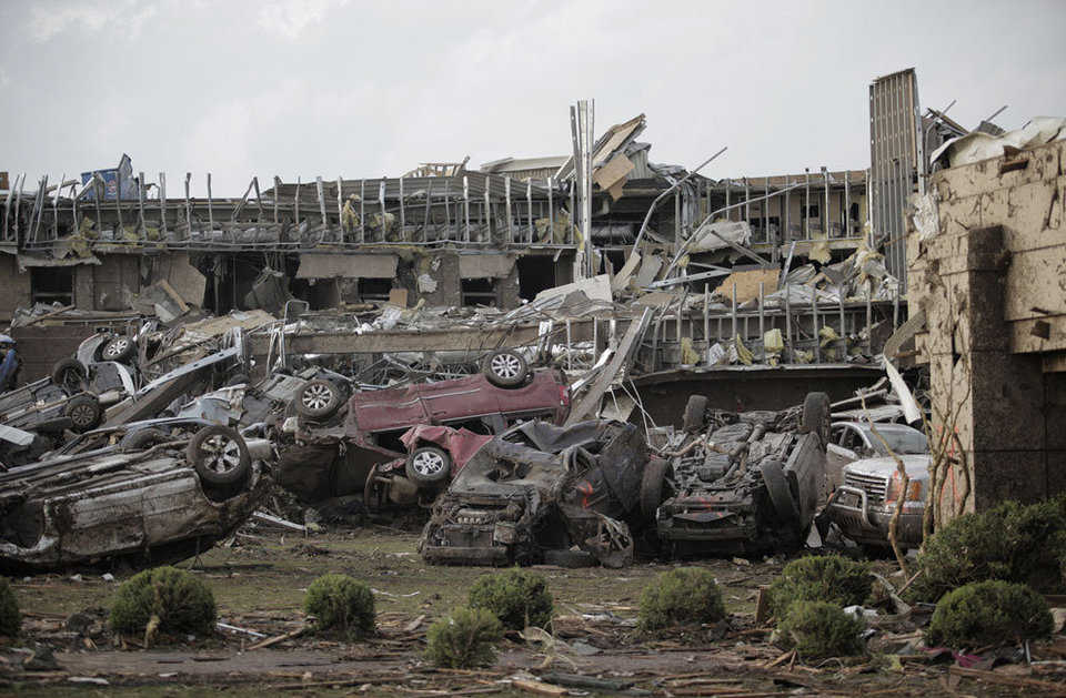 Flipped vehicles are piled up outside the heavily damaged Moore Medical Center on May 20, 2013.