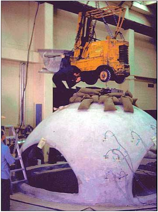Strength testing the Monolithic Dome at BYU Laboratories. The sand bags represent the amount of weight previously thought to be the maximum load this dome could take. The addition of the forklift did nothing. They were ultimately unable to break the shell by overloading it and had to take it apart with jackhammers.