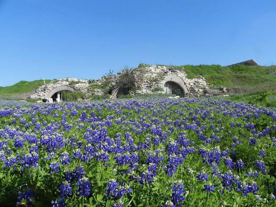 The Texas Blue Bonnets accentuate this picturesque, bermed Monolithic Dome home. Lovely stones surrounding the openings enhance the natural look.