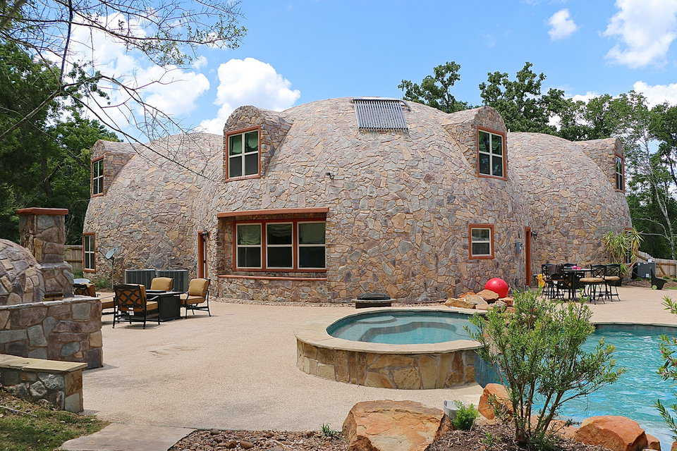 The Monolithic Dome's back patio area features a hot tub and pool, two waterfalls, seating areas with several chairs surrounding a fire pit, a dome-shaped pizza oven which was constructed to match the houses stone-like exterior and a large, covered grilling area. There is also a guest dome and a composting ball.