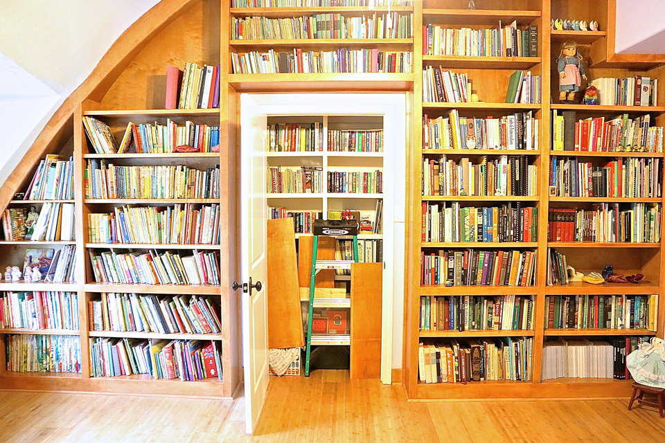 A door built into the bookshelves appears to lead to another room but it is actually a storage closet for even more books, making this a Monolithic Dome reading paradise.