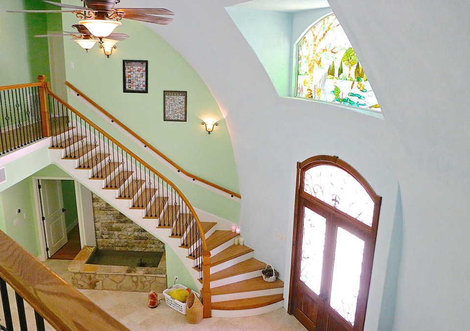 The view from the railing on the second-floor hallway of the Whiteacre's Monolithic Dome Home overlooks the entirety of the front foyer. The expertly built staircase follows the curve of the dome and the rectangular, rock-covered fountain beneath the staircase can be appreciated.
