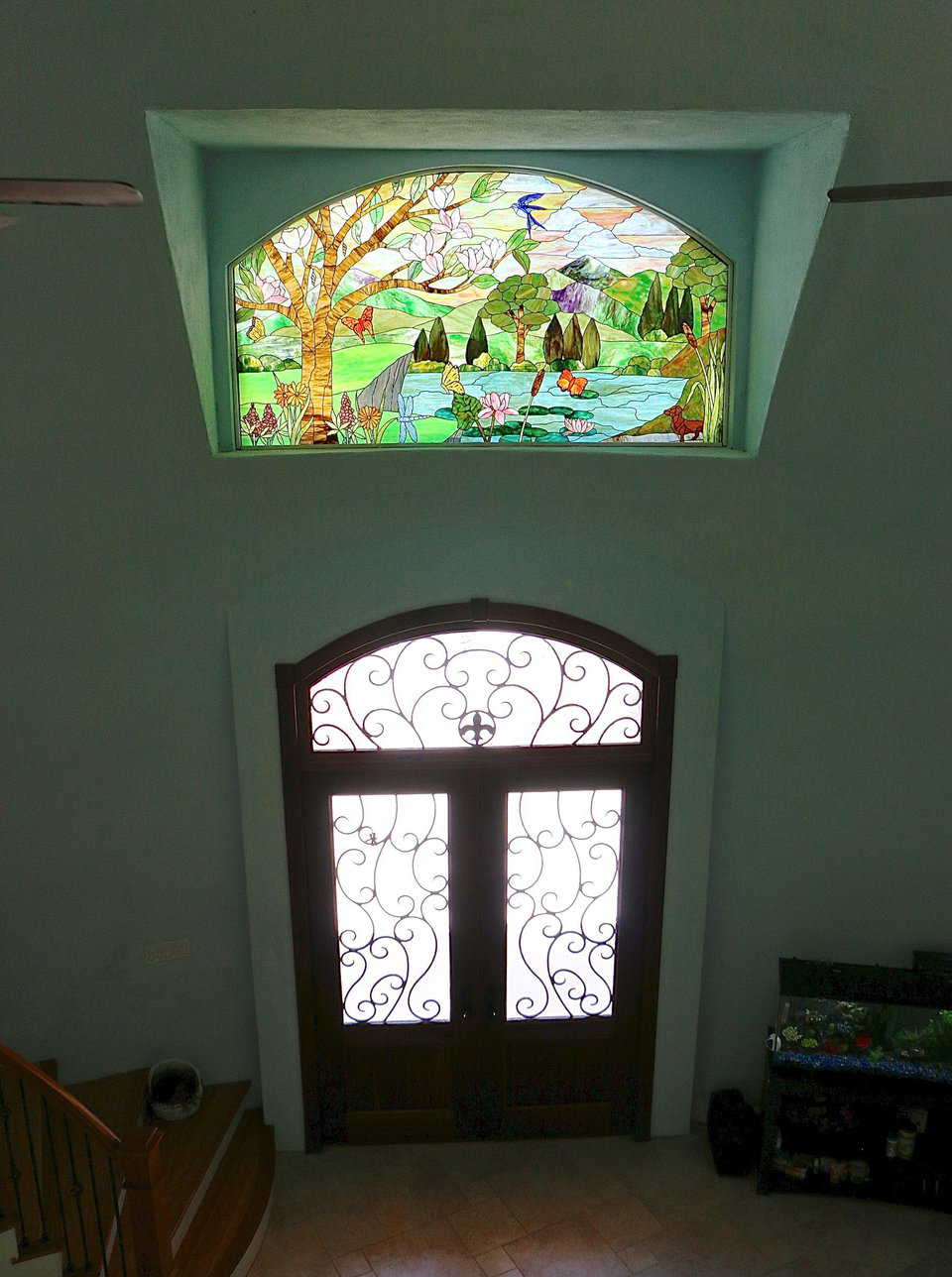 The stained glass window above the front door of the Monolithic Dome Home can be seen clearly from the second floor railing. This window was a gift from the Whiteacre's children who designed it themselves. The details in the design have special meaning to the Whiteacre family.